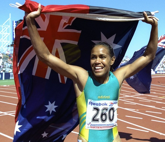4. Cathy Freeman carries the Aboriginal and Australian flags on victory laps at Victoria 1994
