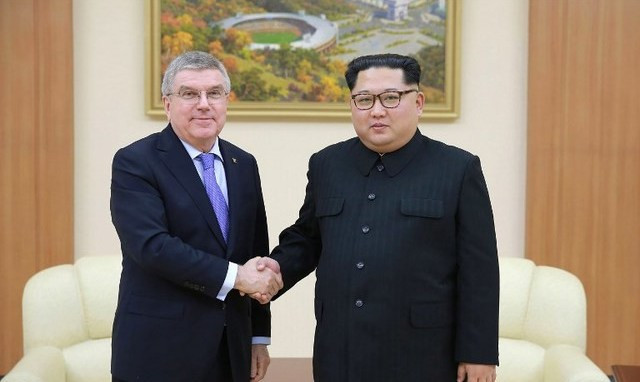 Thomas Bach, left, alongside Kim Jong-un during his visit ©AFP/Getty Images