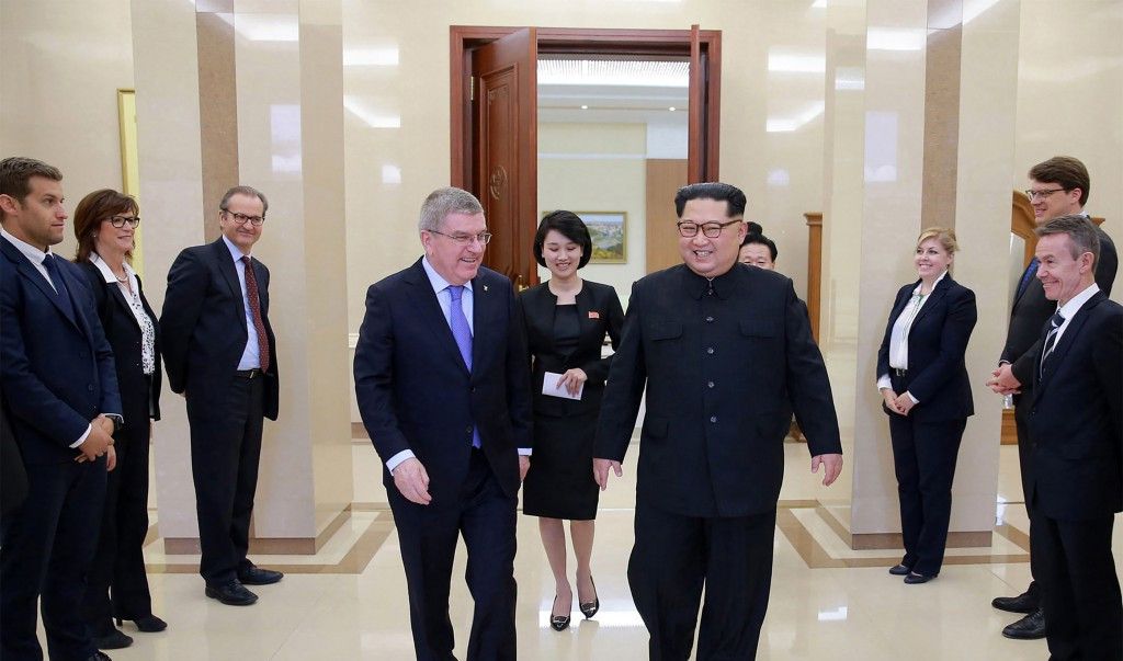Thomas Bach speaks with Kim Jong-un surrounded by members of the IOC delegation ©AFP/Getty Images