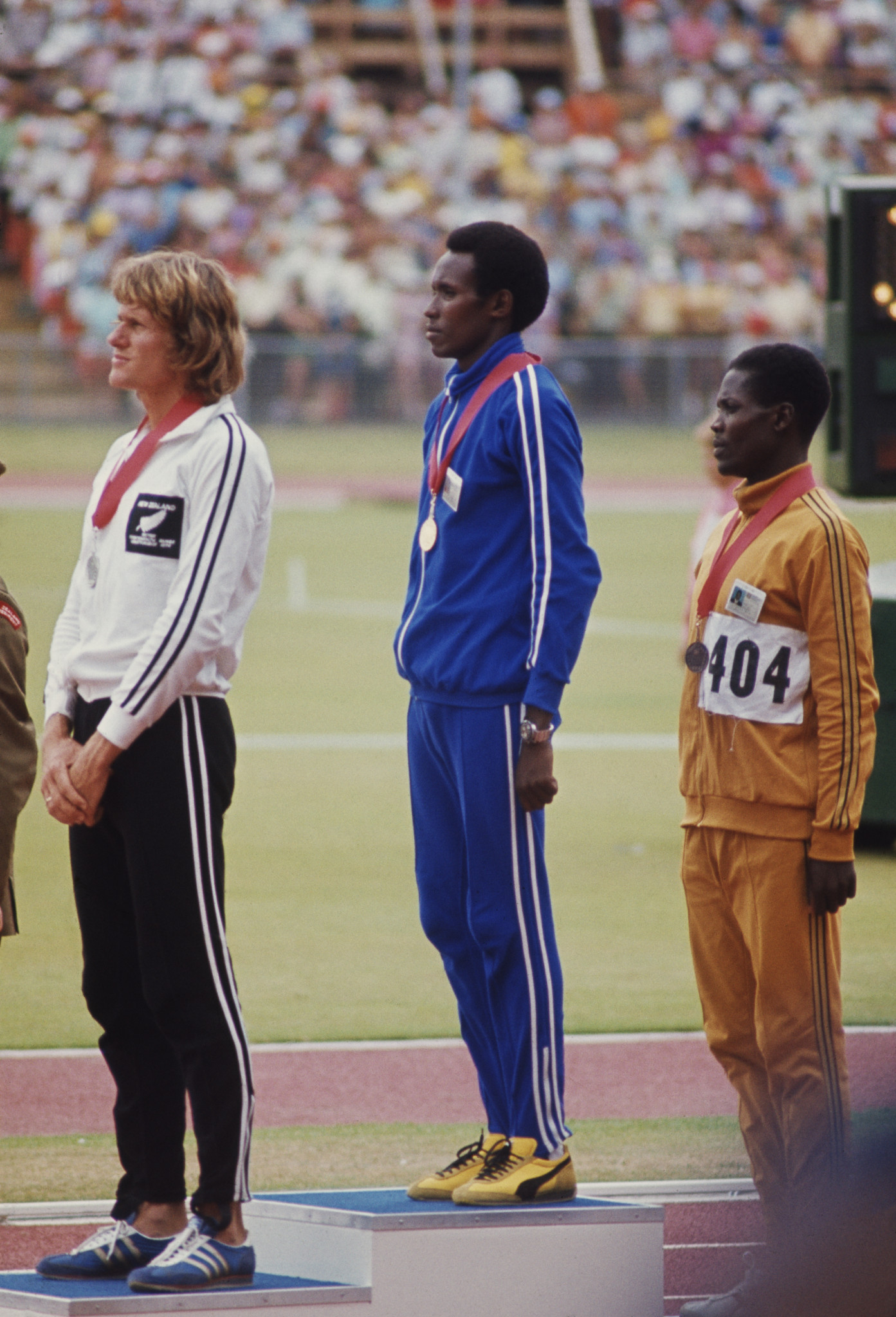 Filbert Bayi, centre, listens to Tanzania's national anthem after winning the Commonwealth Games gold medal in the 1,500m at Christchurch 1974 and beating New Zealand's John Walker, left, in a legendary race ©Getty Images