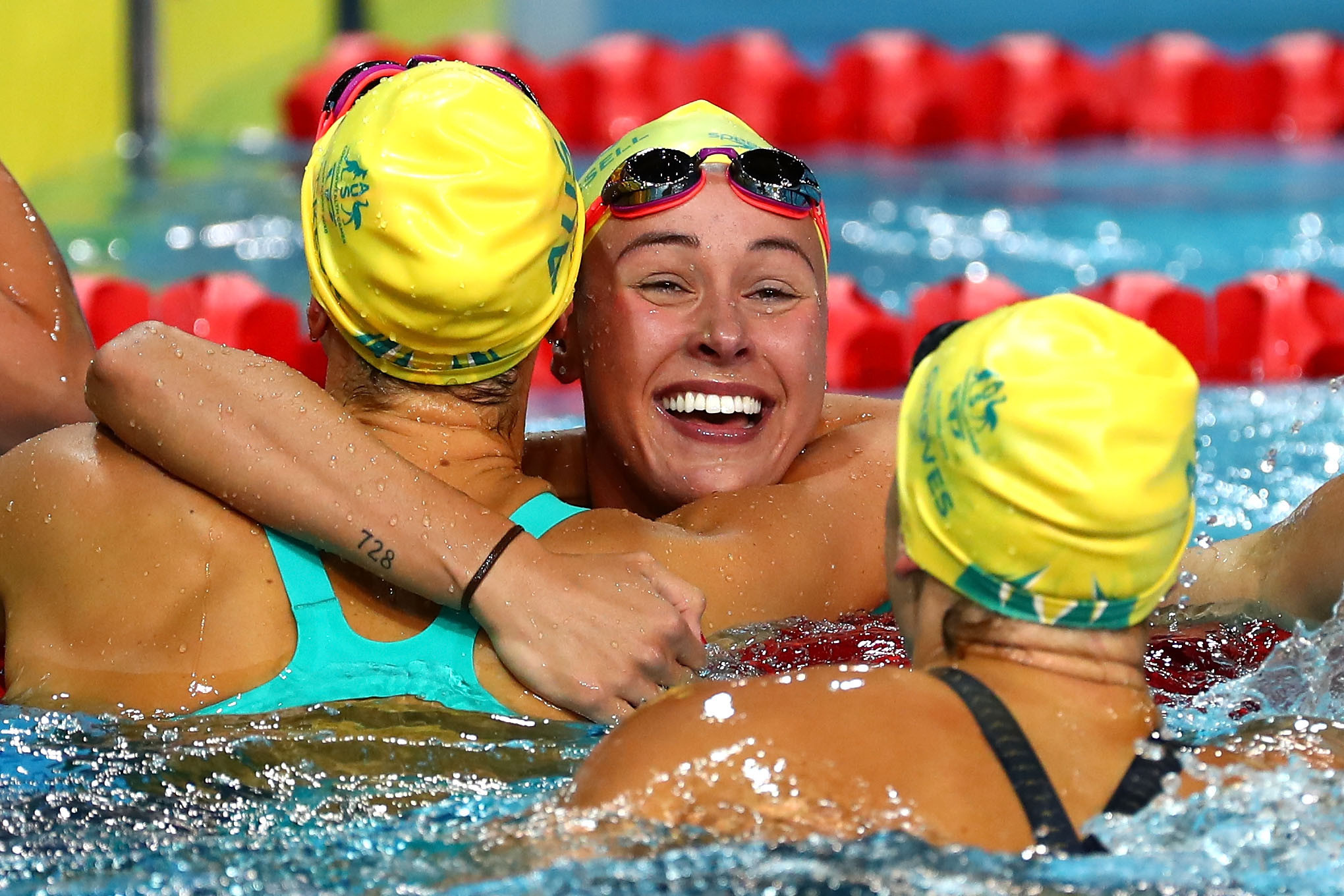 Emma McKeon celebrates in between her two team-mates after the Australian clean sweep ©Getty Images
