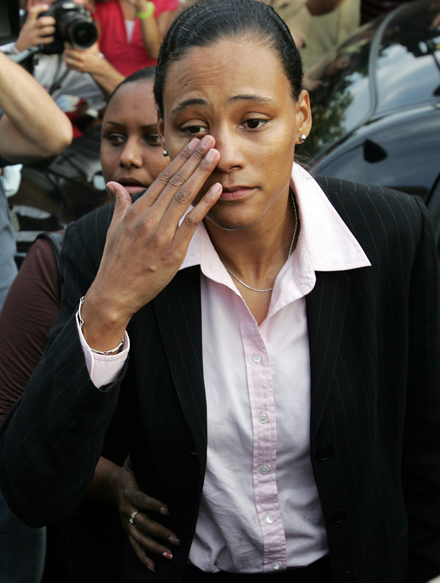 Marion Jones wipes tears from her eyes as she departs a US District Court on October 5 2007 having admitted to steroid abuse ©Getty Images