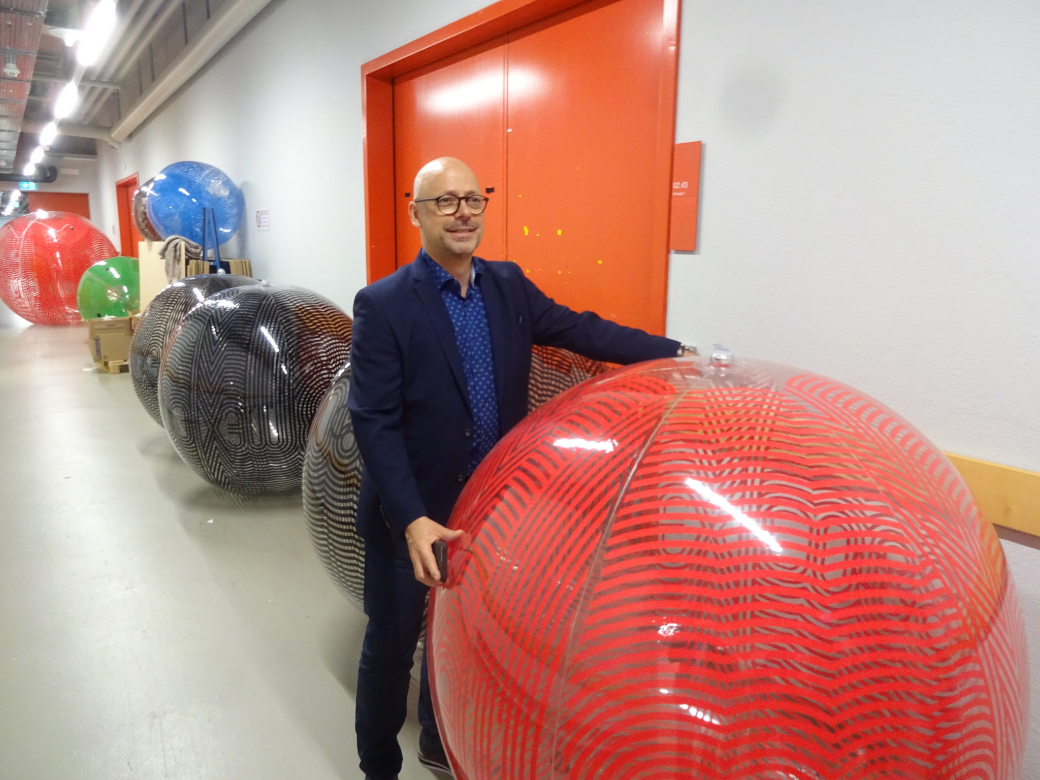 Curator Markus Osterwalder with a giant ball from Mexico 1968 before it was installed in the exhibition ©Philip Barker