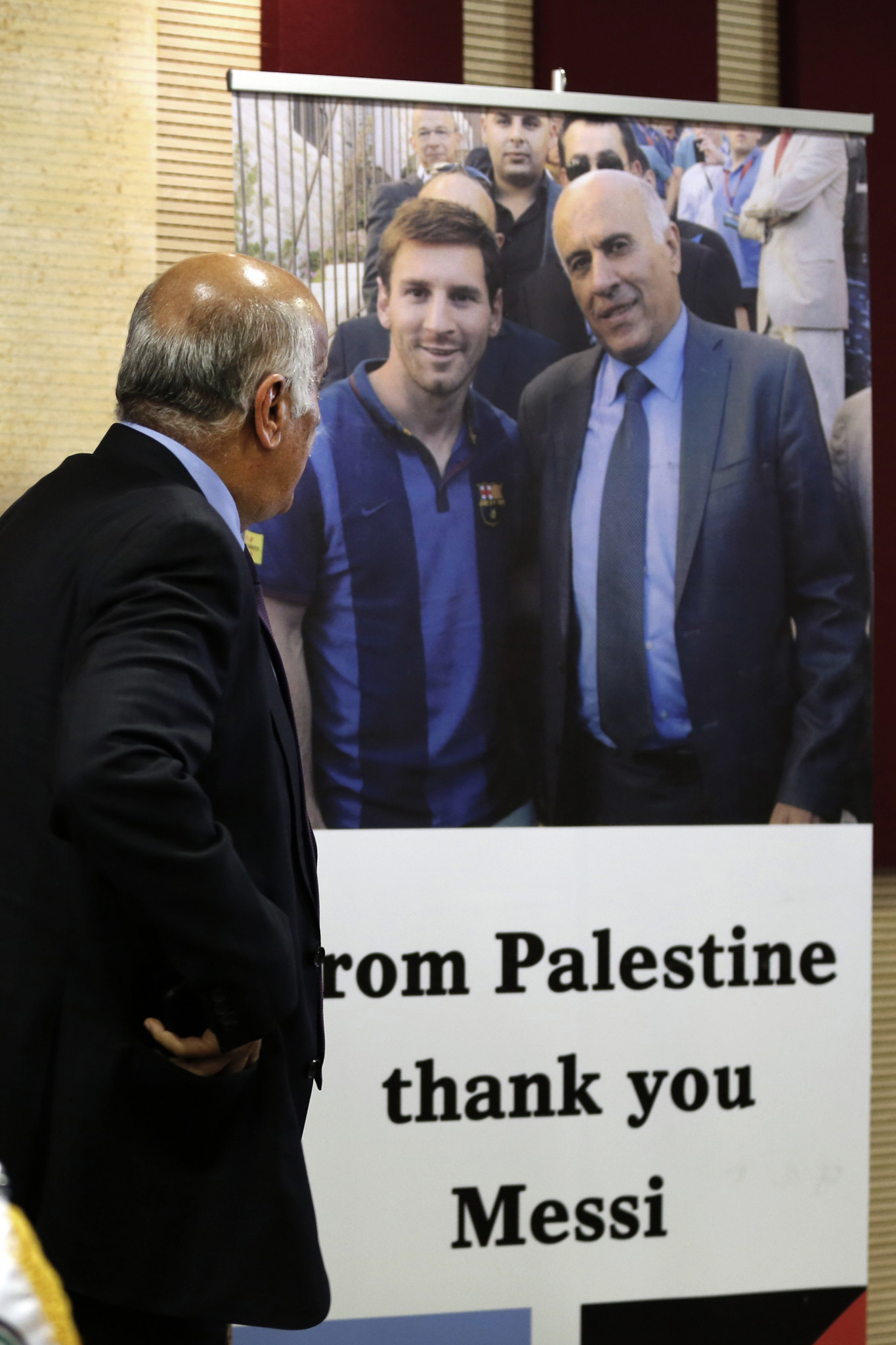 Palestine football boss Jibril Rajoub stands in front of a sign addressed to Argentina's star player Lionel Messi, left ©Getty Images