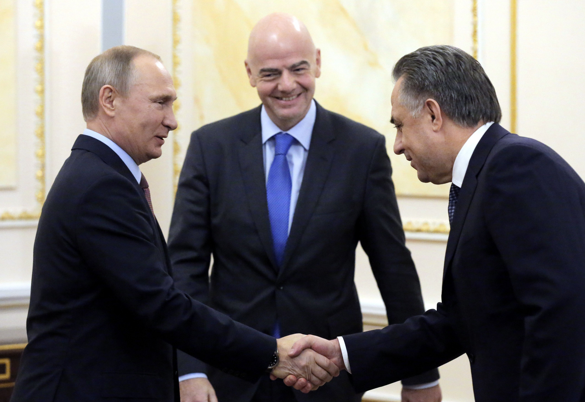 Vladimir Putin, left, and Vitaly Mutko, right, either side of FIFA President Gianni Infantino ©Getty Images