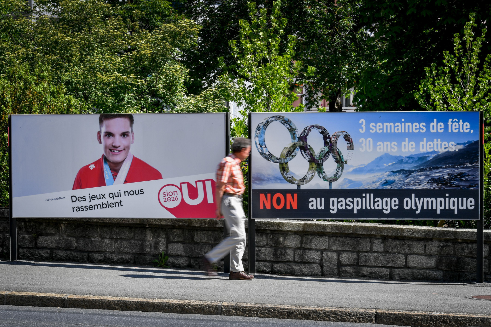 Posters supporting and opposing the Sion 2026 bid placed side by side ©Getty Images
