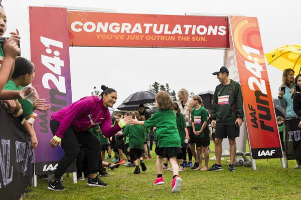 New Zealand's double Olympic shot put champion Valerie Adams congratulates finishers in the IAAF Run 24:1 run in Auckland - the event which started the new challenge ©IAAF