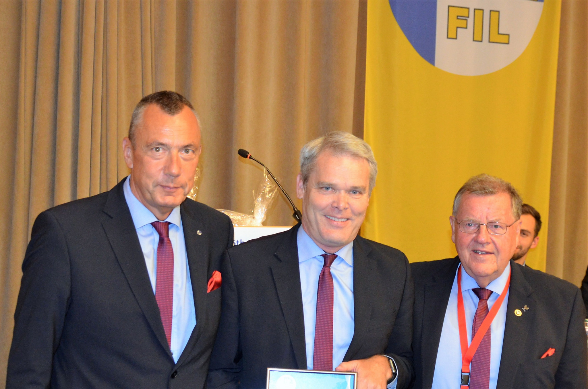 Departing secretary general Svein Romstad, centre, has been named an honorary member of the International Luge Federation ©FIL