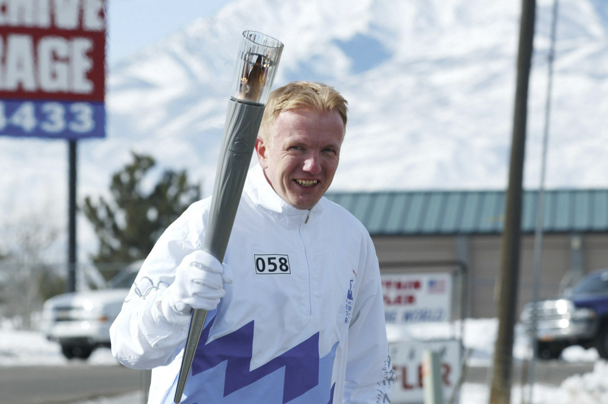 Roland Baar pictured carrying the Olympic Torch before the Salt Lake City 2002 Olympics ©Getty Images