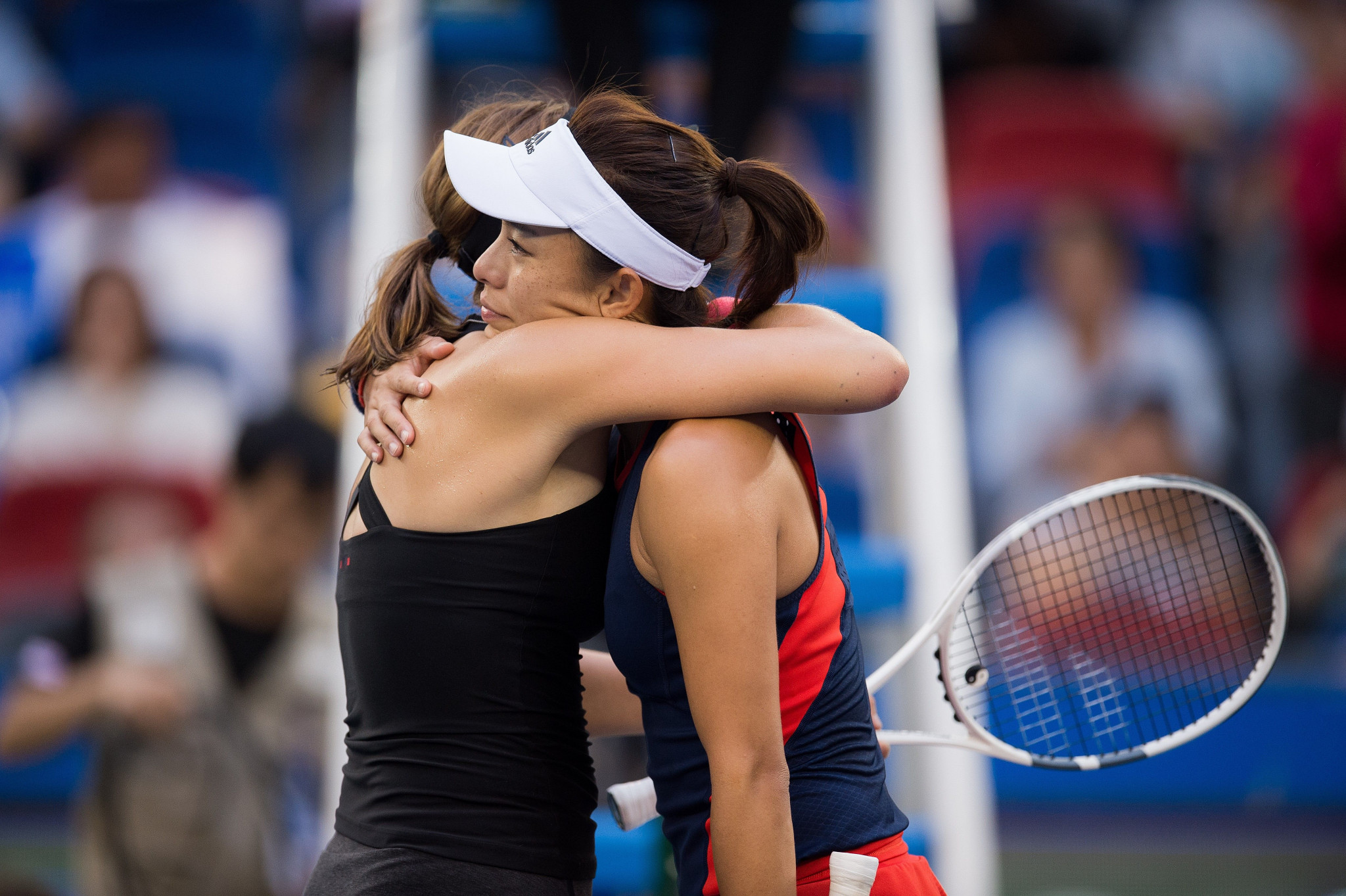 Wang Qiang, right, is hugged by Annet Kontaveit after retiring because of a thigh injury ©Getty Images