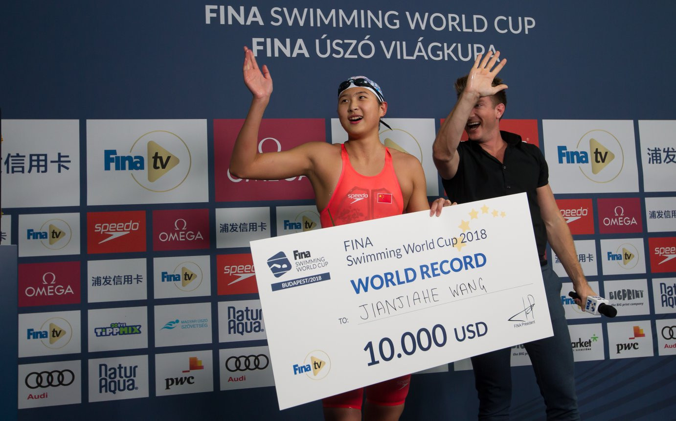 China's Jianjiahe Wang receives a prize cheque for breaking the world record in the 400m freestyle at the FINA Swimming World Cup ©FINA