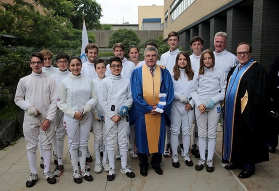 Marcel Aubut (right) pictured alongside Thomas Bach and young athletes during a graduation ceremony in Montreal in July ©ITG