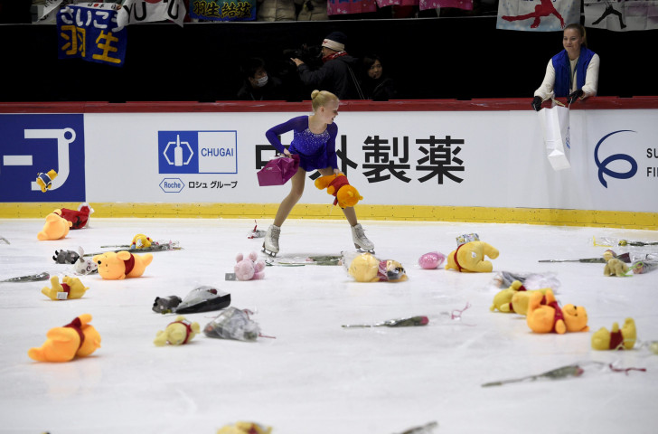 A flower girl collects gifts, thrown onto the ice at the Helsinki Arena after Yuzuru Hanyu's world record short programme performance tonight ©Getty Images