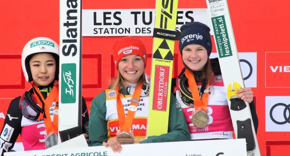 Germany's Katharina Althaus on the podium after her Ski Jumping World Cup victory in Premanon, France ©FIS
