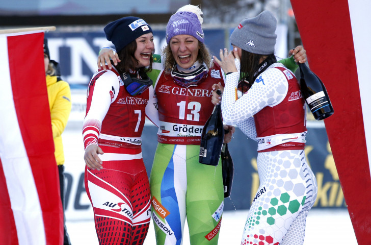 Ilka Stuhec of Slovenia, back after a 20-month absence through injury, celebrates victory in the FIS World Cup downhill in Val Gardena with her fellow medallists ©Getty Images