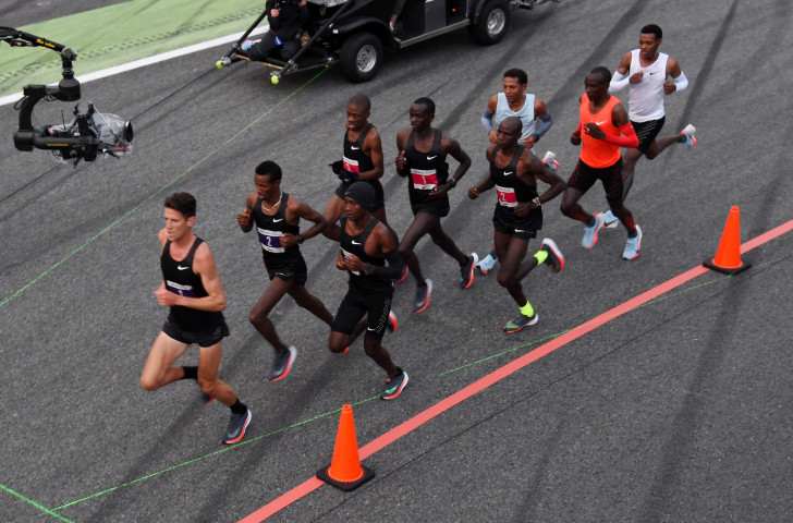 Eliud Kipchoge, in the orange vest, runs behind a phalanx of pacemakers at the Monza race track in 2017 as part of Nike's Breaking2 project ©Getty Images