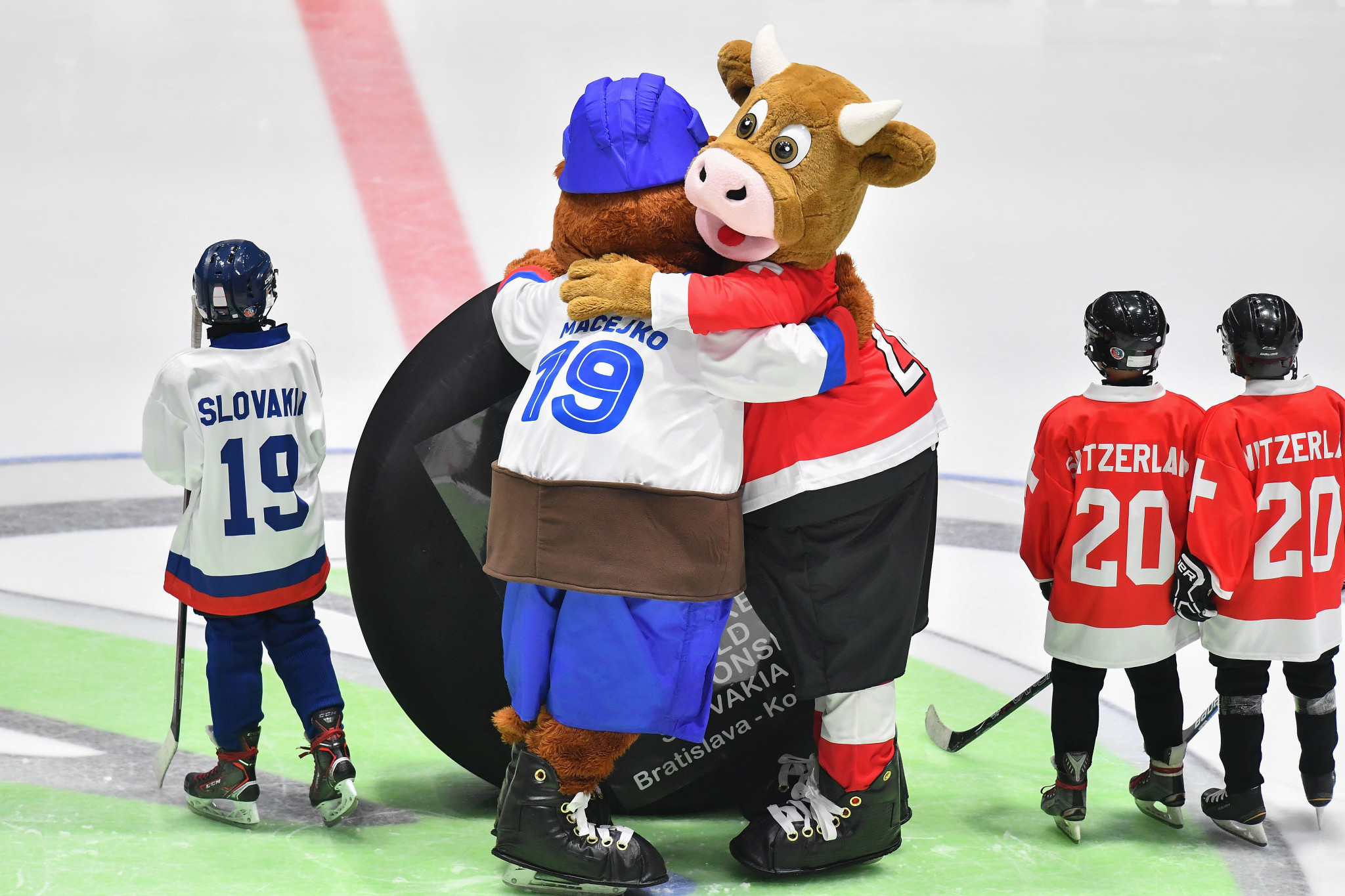 Slovakian mascot Macejko passes Swiss mascot Cooly a giant puck at the final of the International Ice Hockey Federation World Championship in Bratislava ©Getty Images