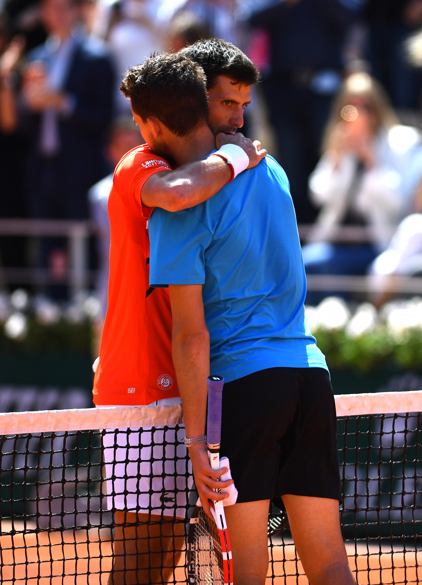 Thiem and Djokovic embrace at the end of their five-set semi-final battle ©Getty Images