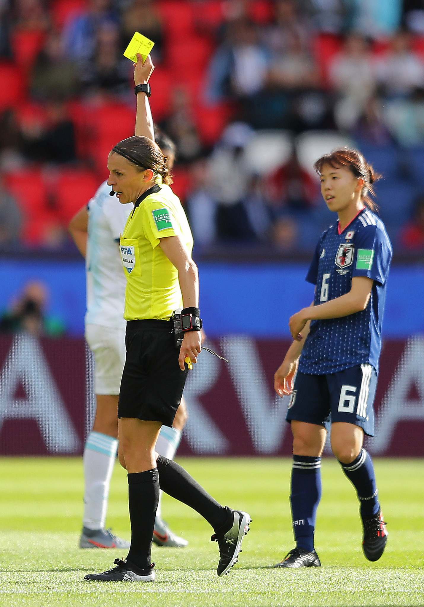 French referee Stephanie Frappart shows Hina Sugita of Japan a yellow card ©Getty Images