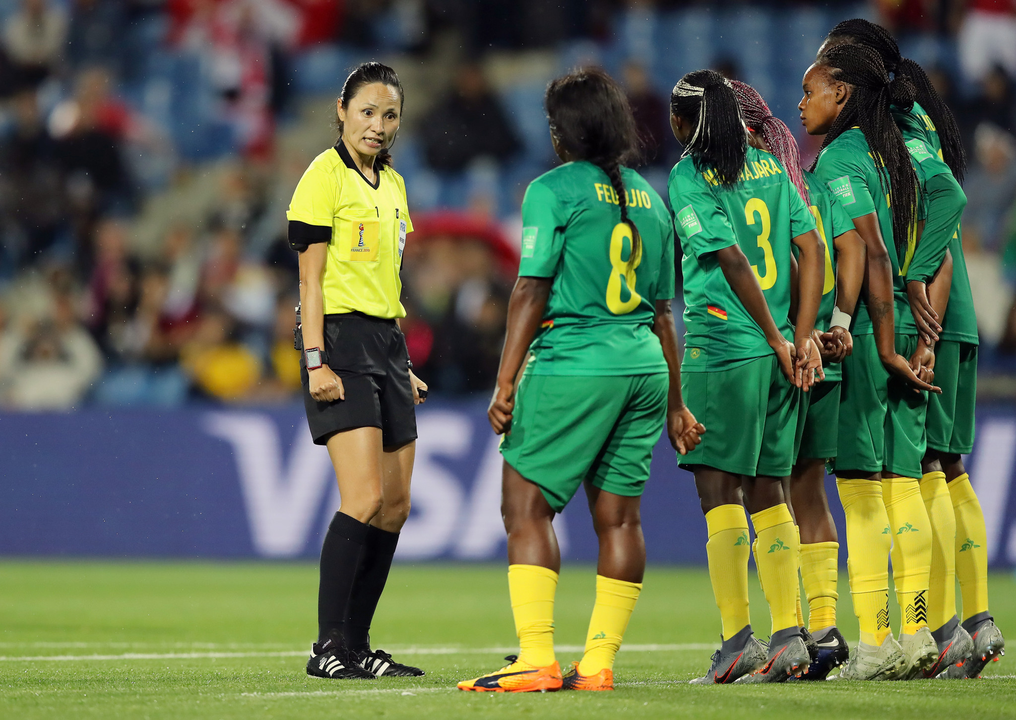 Referee Ri Hyang Ok speaks with the Cameroon defenders as they form a wall against Canada ©Getty Images