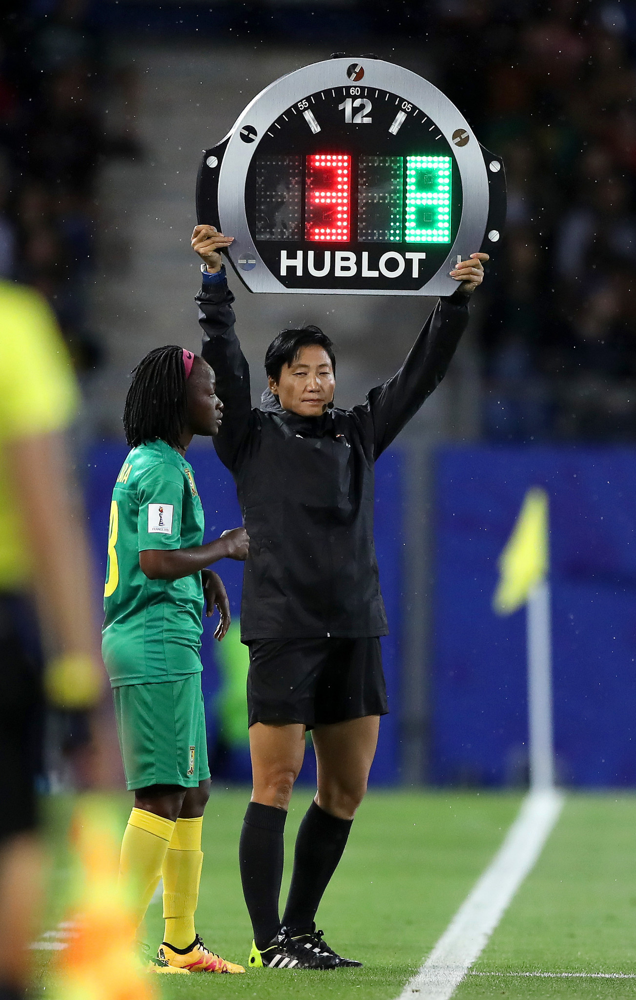 Fourth Official Liang Qin uses the electronic board to indicate a substitution as Cameroon sought a way back into the match ©Getty Images