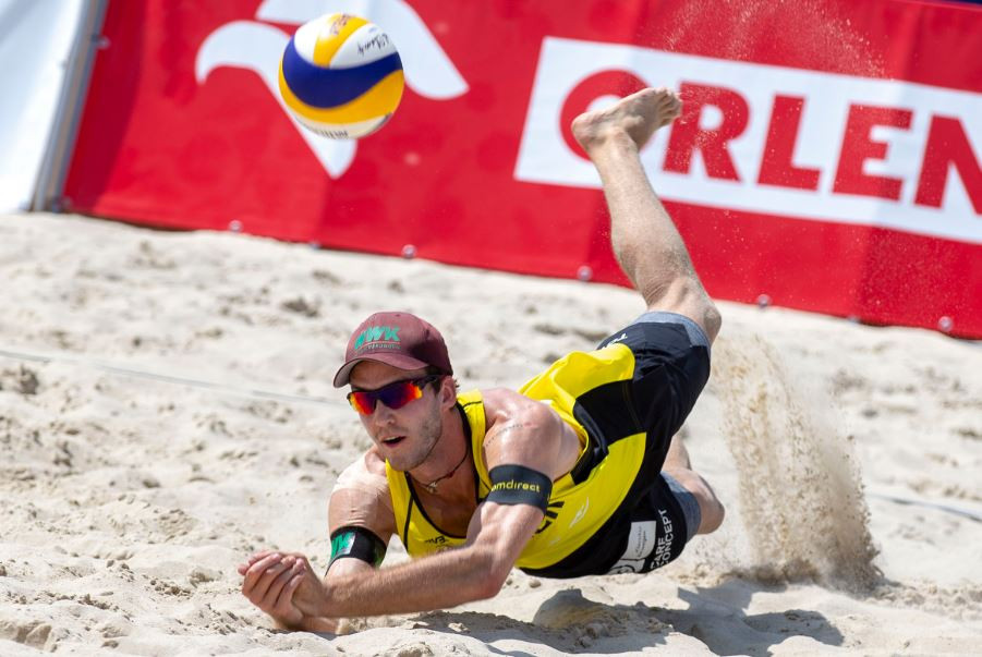 Germany's Clemens Wickler makes a low save in his match against Americans Nicholas Lucena and Philip Dalhausser ©FIVB