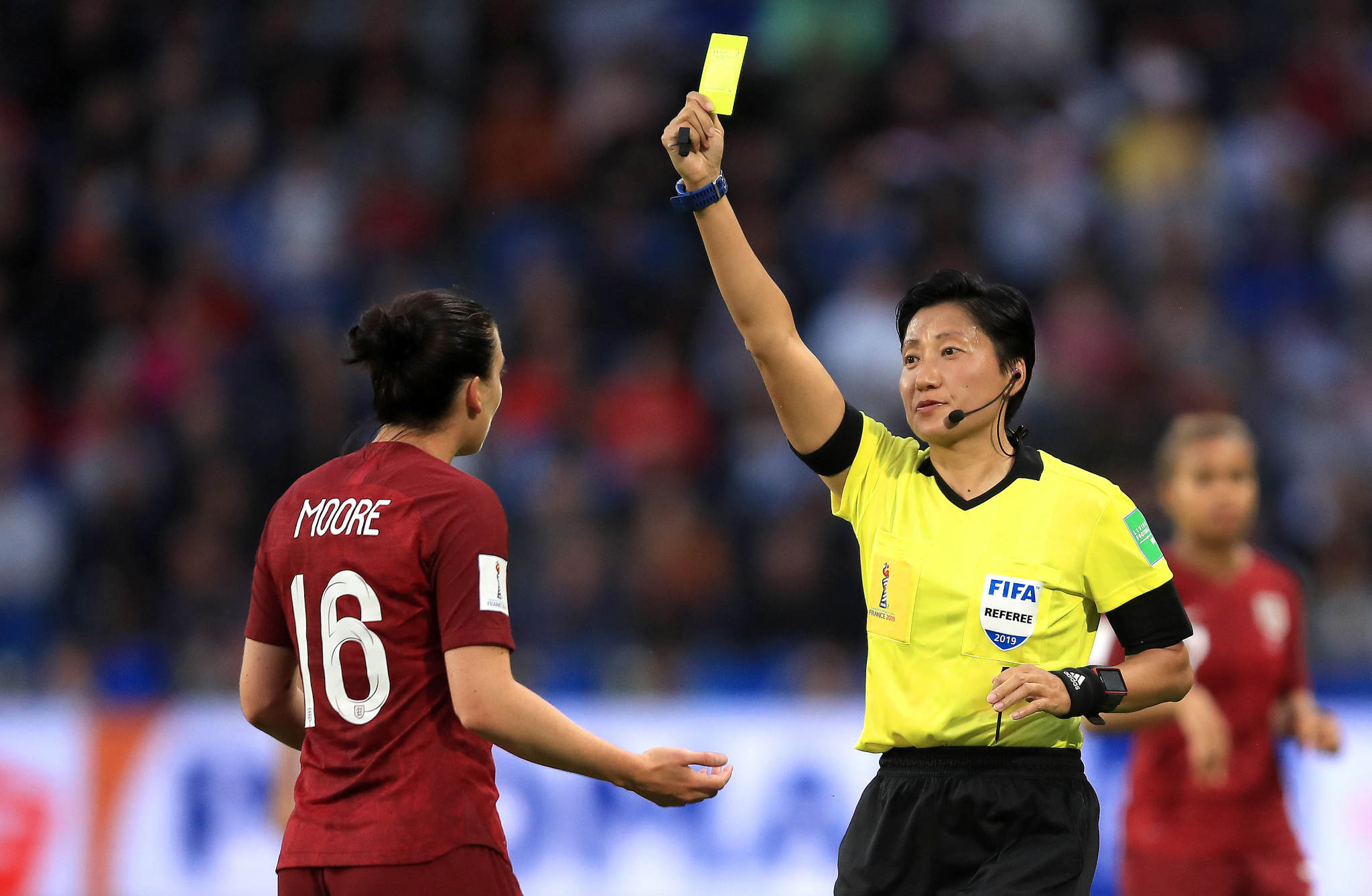 Referee Liang Qin shows Jade Moore of England a yellow card ©Getty Images