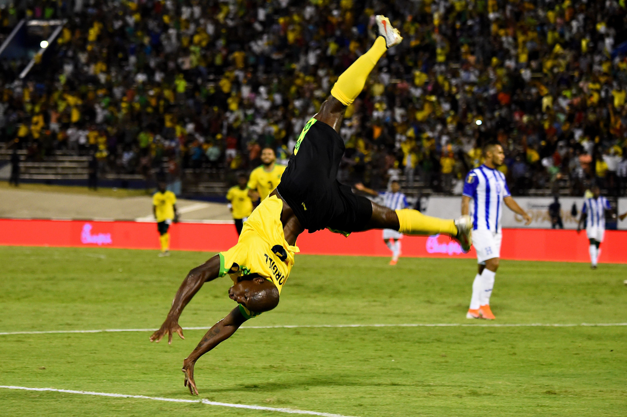 Double goalscorer Dever Orgill takes to the air to celebrate Jamaica's win ©Getty Images