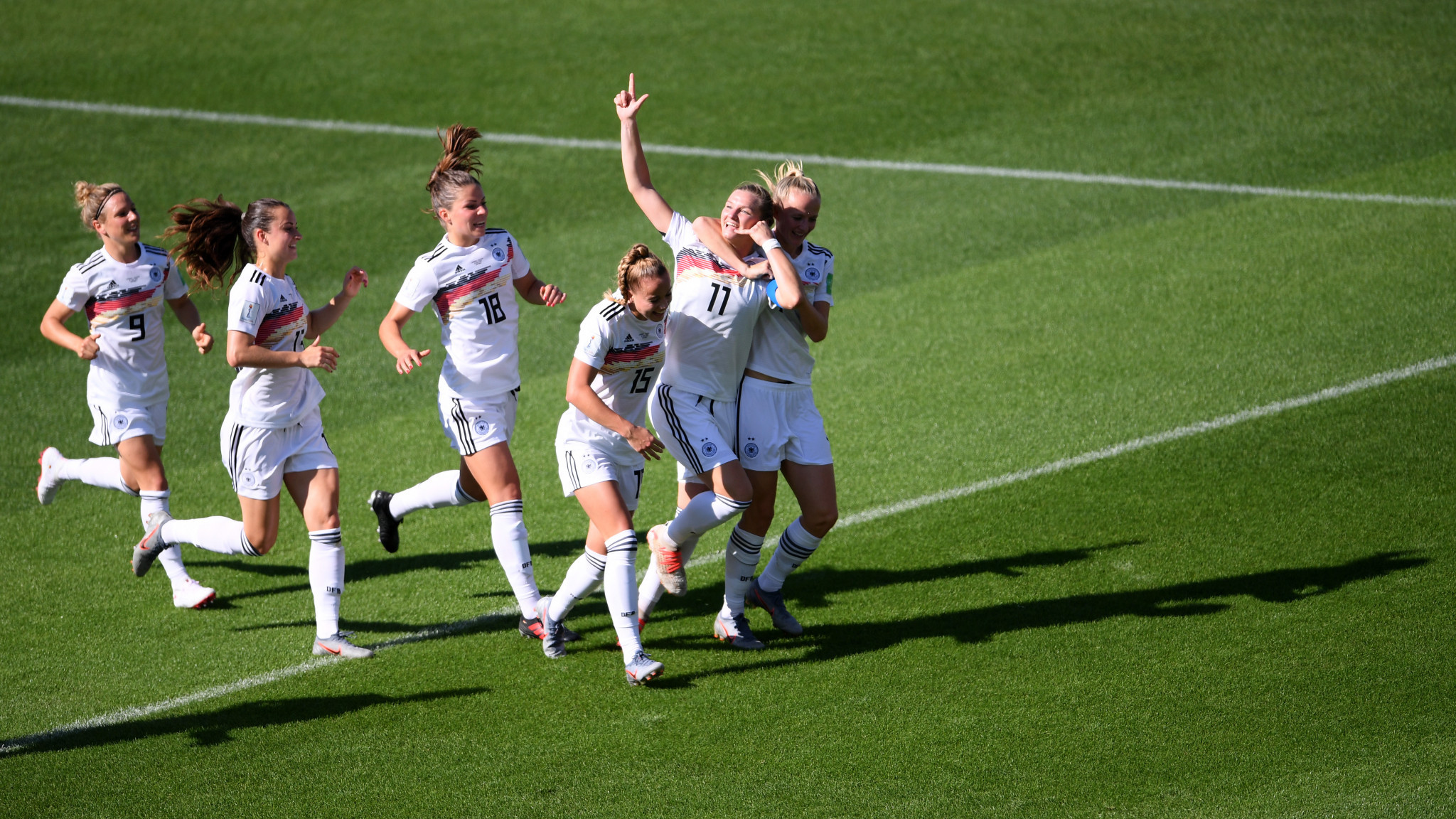 Popp is mobbed by her team mates after her header opened the scoring in Grenoble ©Getty Images
