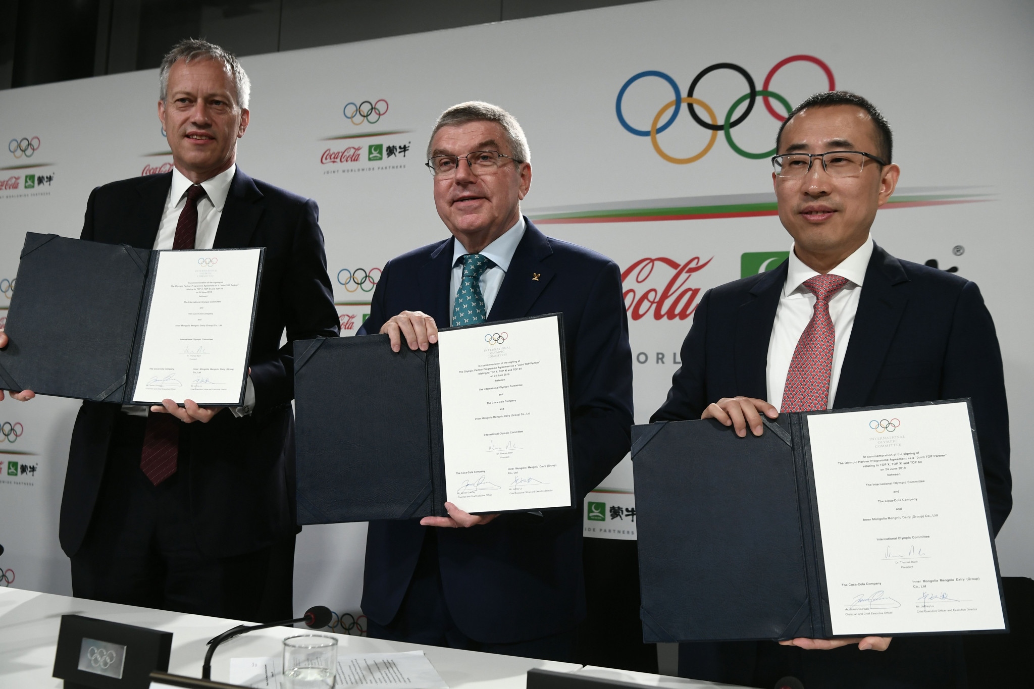 IOC President Thomas Bach, centre, shows off the newly-signed contract with Coca-Cola chief executive and chairman James Quincey, left, and Jeffrey Lu, chief executive of Mengniu, right ©Getty Images