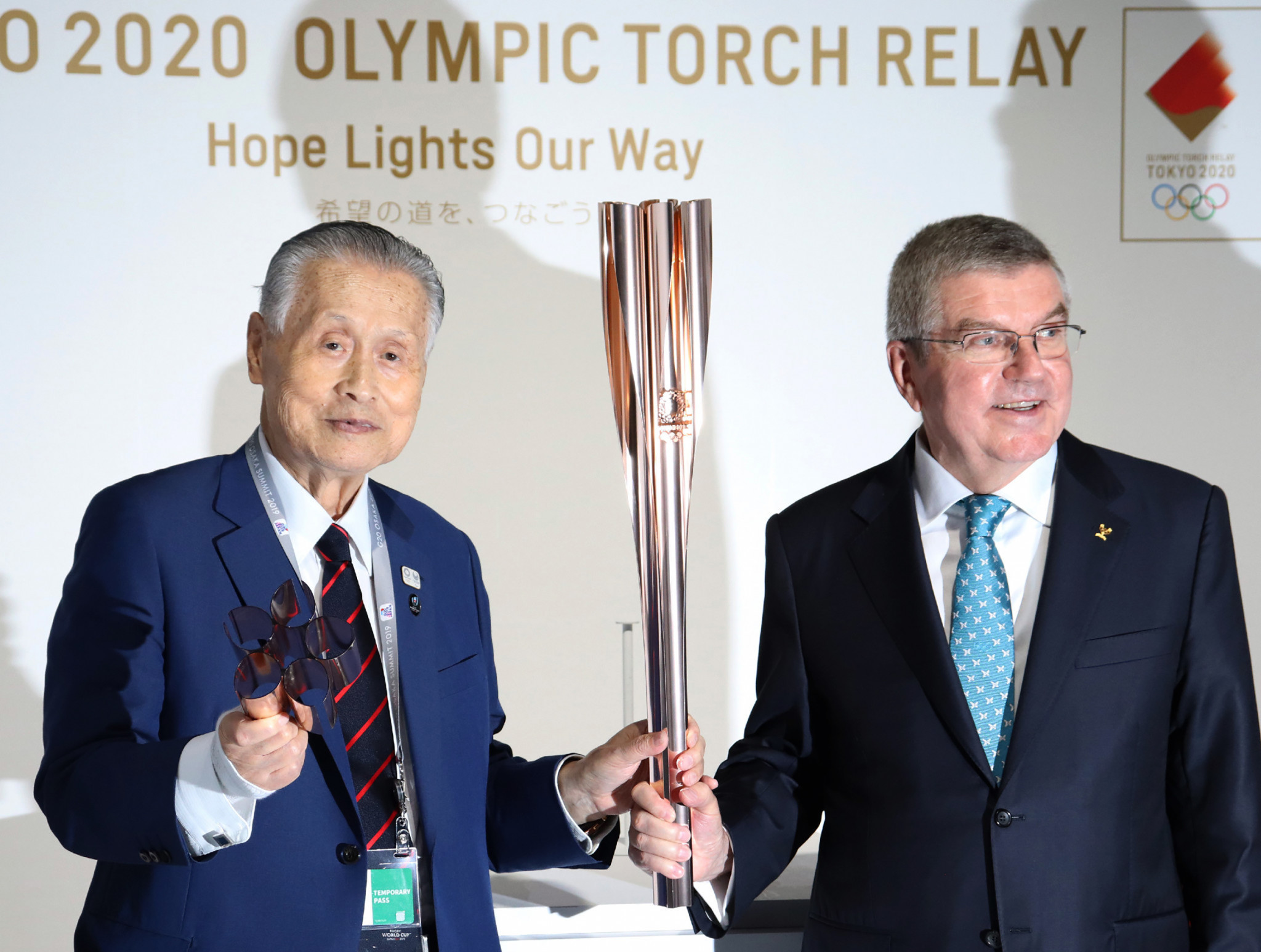 International Olympic Committee President Thomas Bach, right, and Tokyo 2020 President Yoshiro Mori pose while holding the Tokyo 2020 Torch at the Olympic promotion booth at the G20 Summit in Osaka ©Getty Images