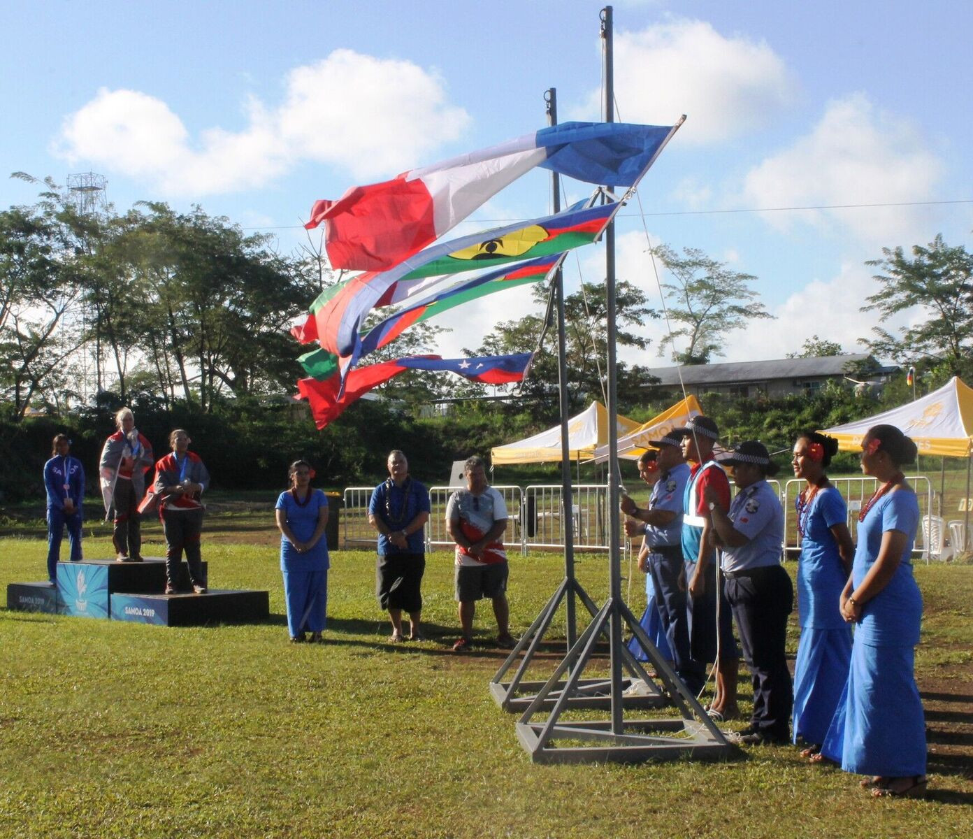 A strong breeze during a medal ceremony at the archery causes the flags to flutter ©Samoa 2019