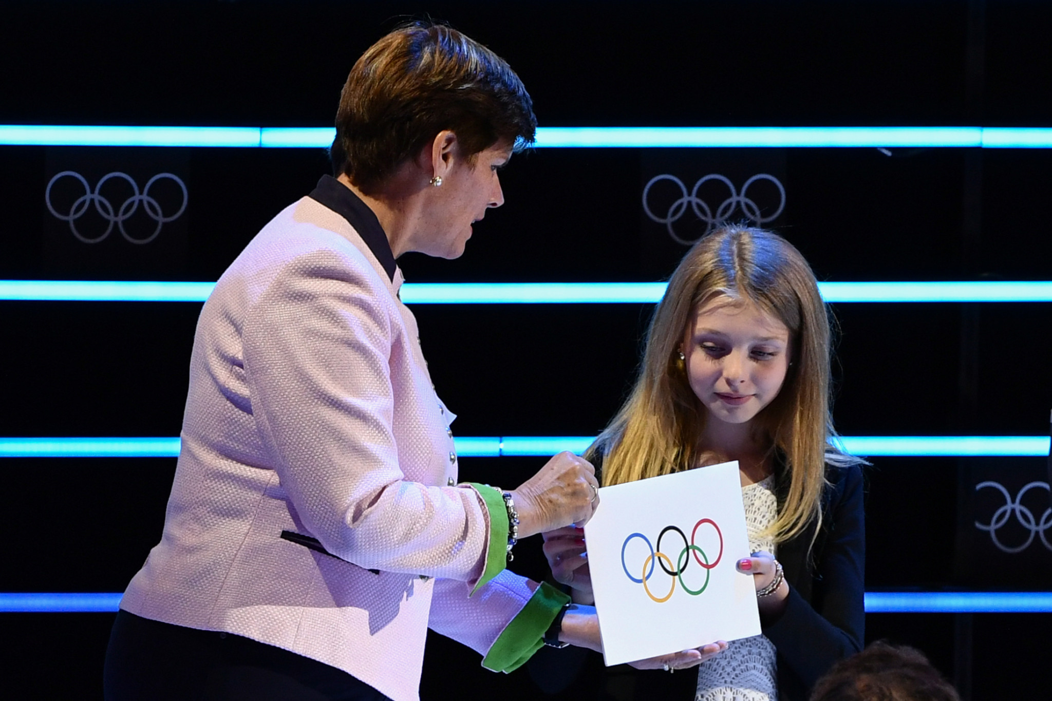 Nicole Hoevertsz gives the envelope containing the name of the winner of the 2026 Winter Olympics to 10-year-old Livia de Bon, a figure skater from Lausanne, who in turn passed it to IOC President Thomas Bach ©Getty Images