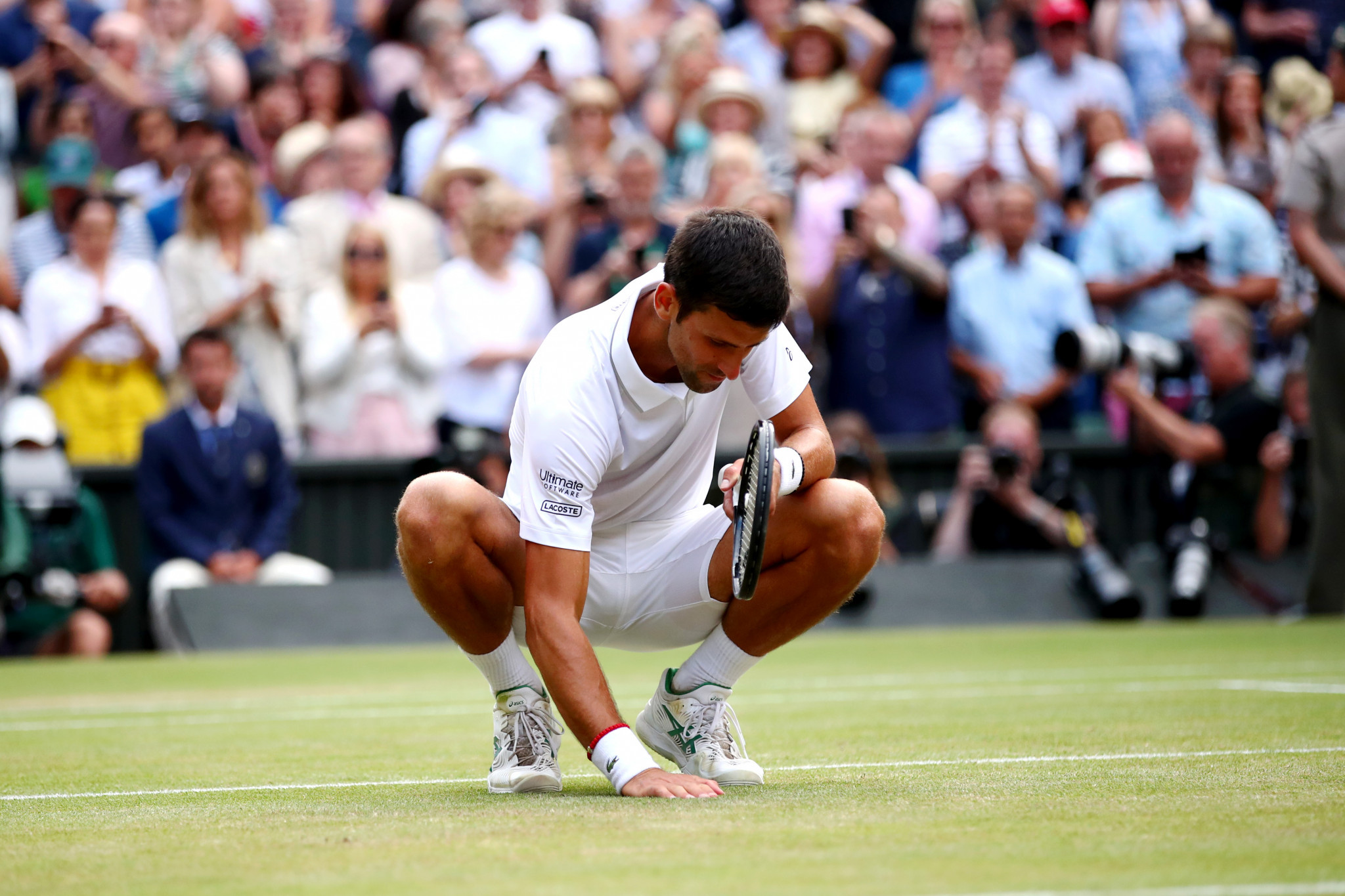 Djokovic celebrated his victory in unusual fashion – by chewing on some of the Wimbledon turf ©Getty Images