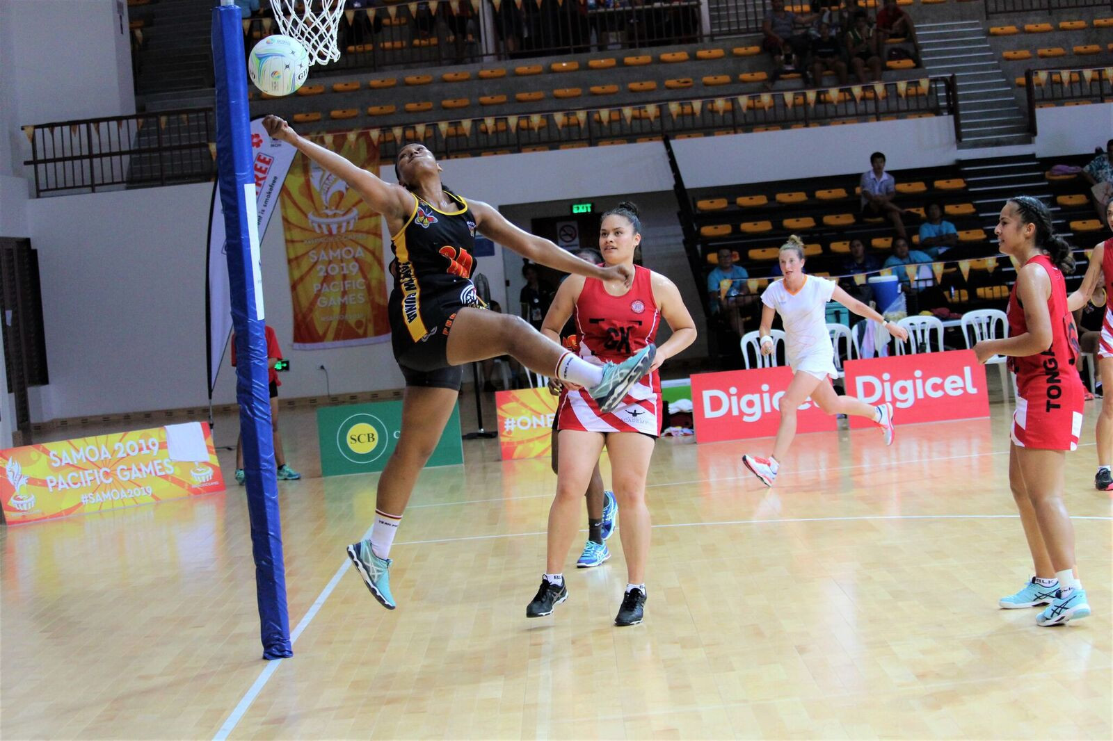 A Papua New Guinea netballer stretches for the ball during their clash with Tonga ©Games News Service