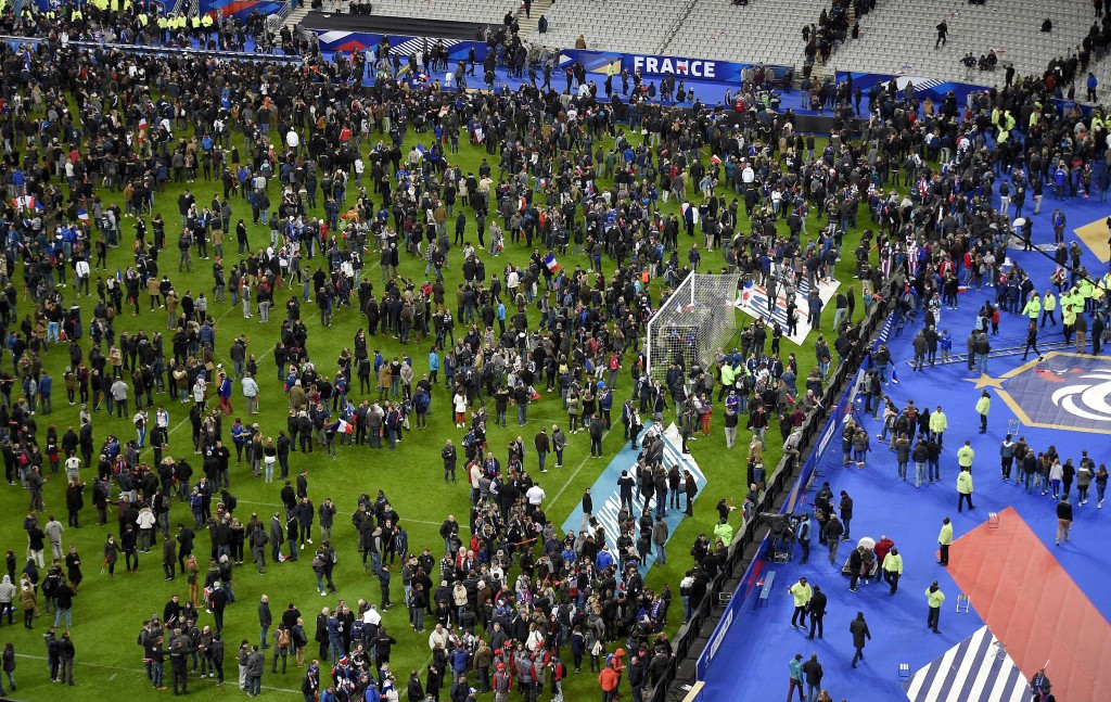 French and Germany fans spill onto the pitch followng explosions at the Stade de France which killed three people as Paris was hit by its worst attack since the end of World War Two