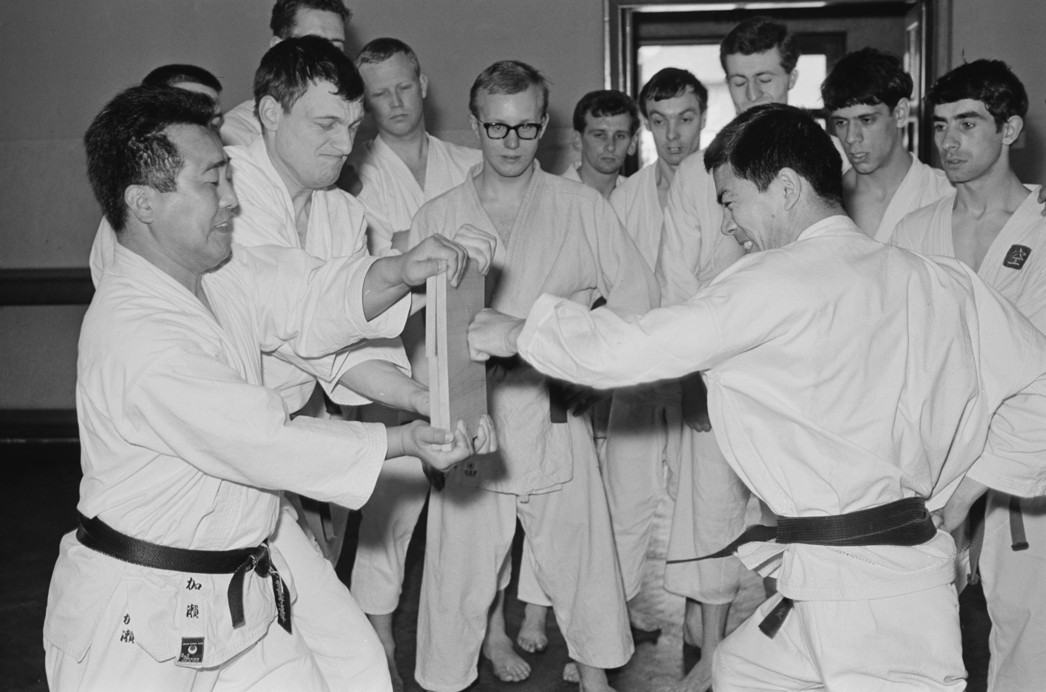 Japanese teacher of Shotokan karate Hirokazu Kanazawa demonstrating the breaking of a piece of wood in front of a group of students, UK, 2nd May 1965 ©Getty Images