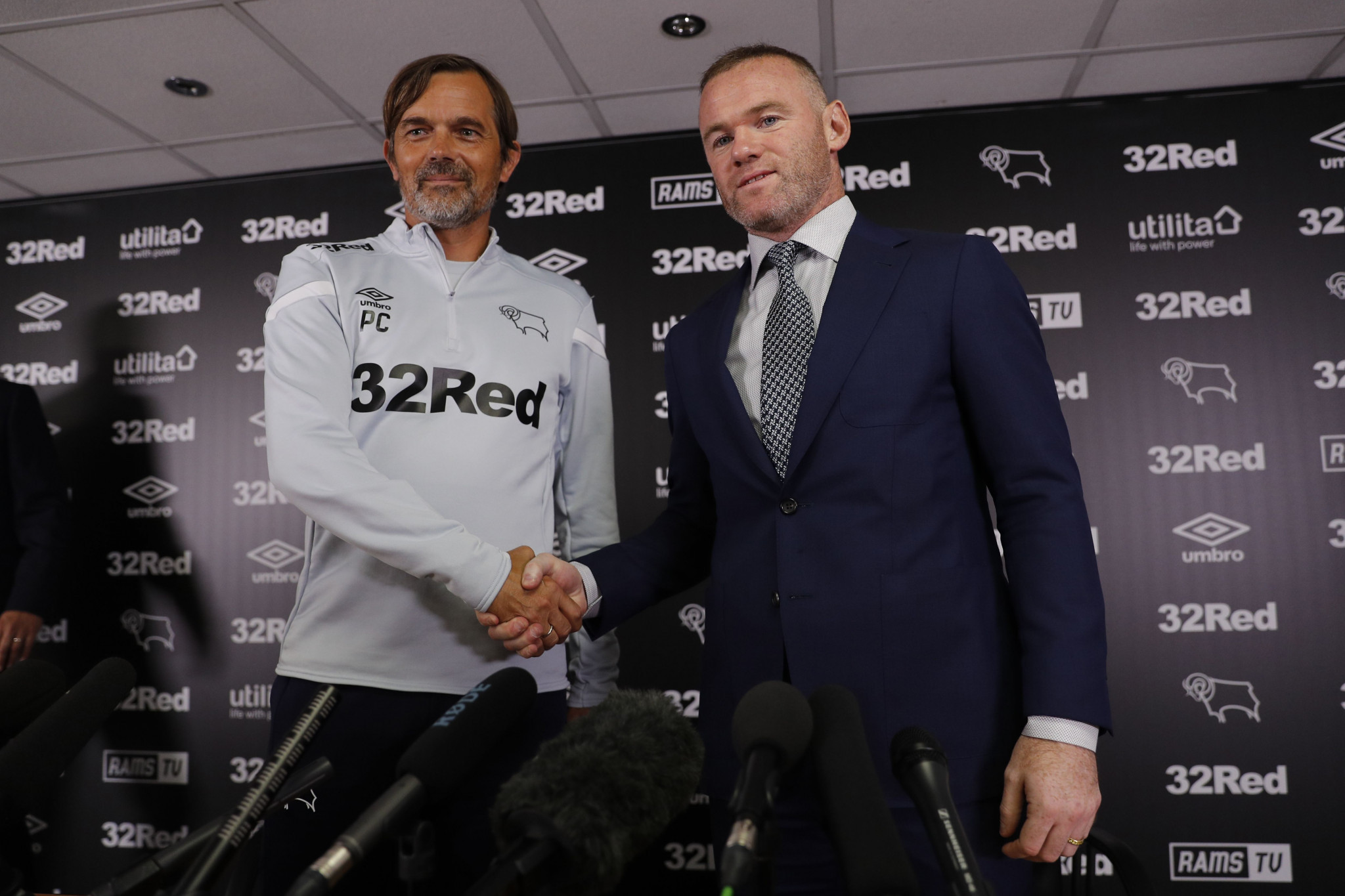 Phillip Cocu, left, shakes hands with new signing Wayne Rooney, who will controversially wear number 32 ©Getty Images