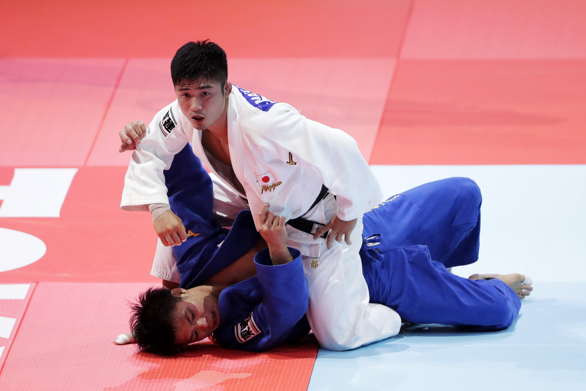 Abe's brother, Hifumi, in blue, lost his world crown in the men's under-66kg competition ©Getty Images