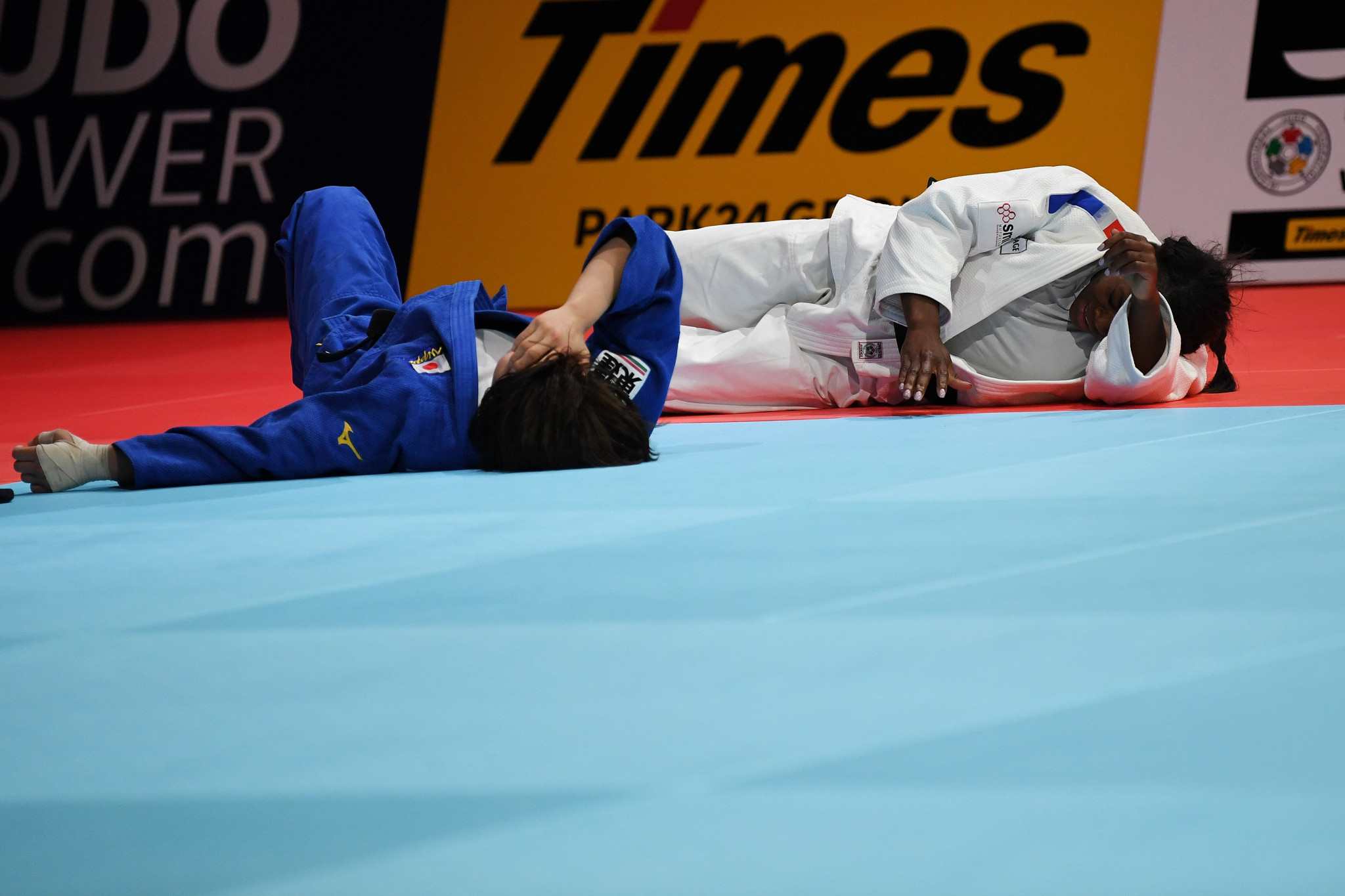 Clarisse Agbegnenou and Miku Toshiro lie prone on the tatami after their astonishing final ©Getty Images