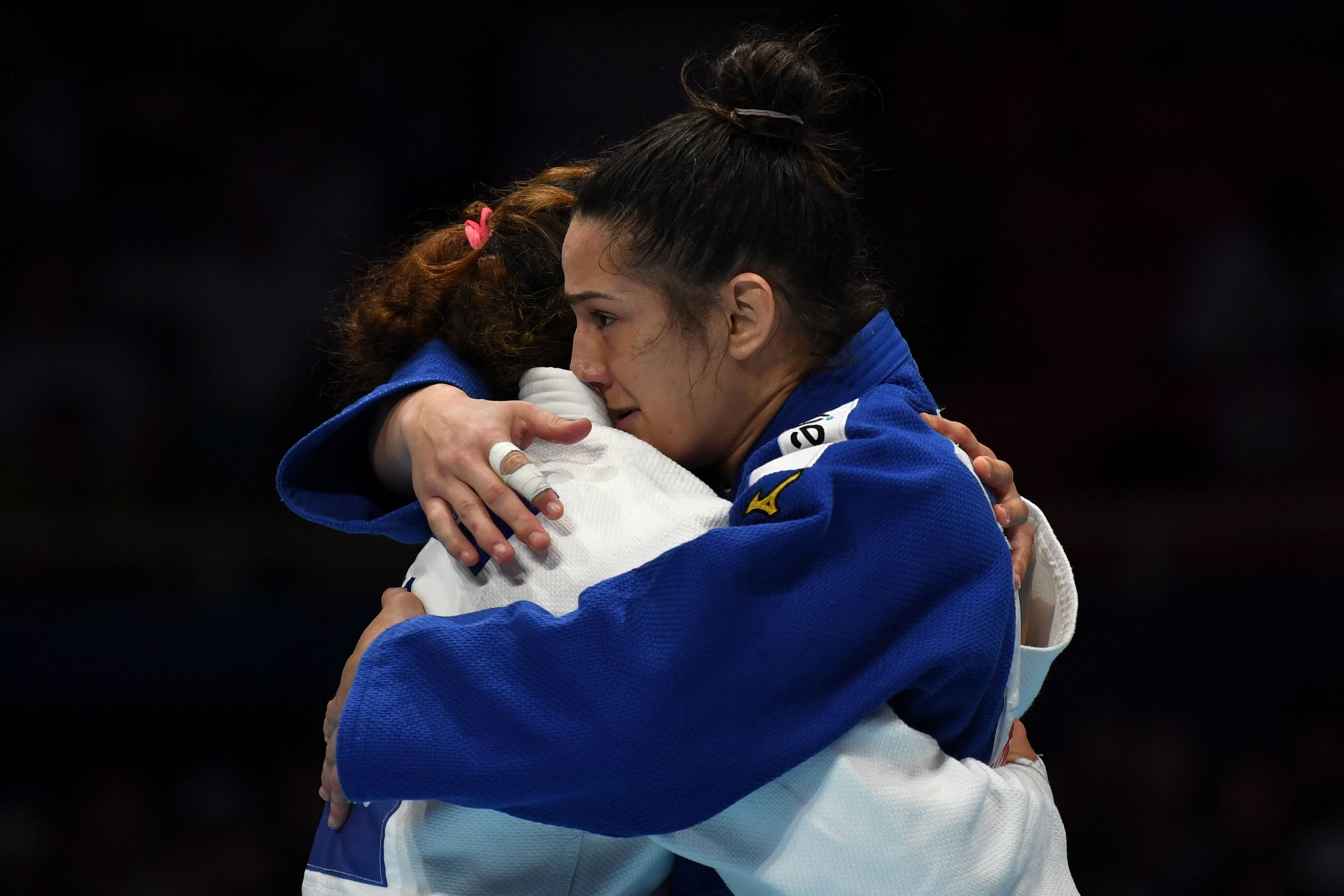 Mayra Aguiar of Brazil, in blue, hugs Patricia Sampaio of Portugal after winning bronze ©Getty Images