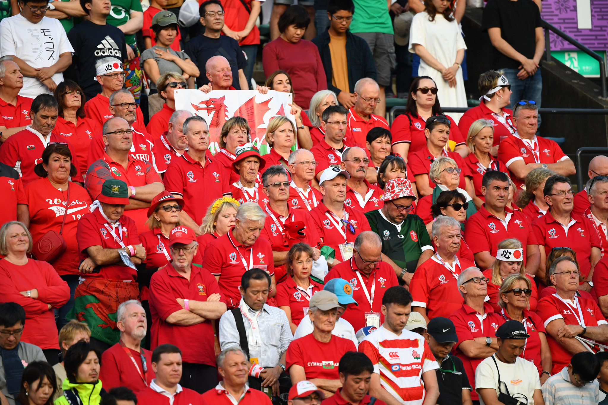 Wales fans observe a moment of silence for victims of Typhoon Hagibis, which has killed 18 people in Japan over the weekend ©Getty Images