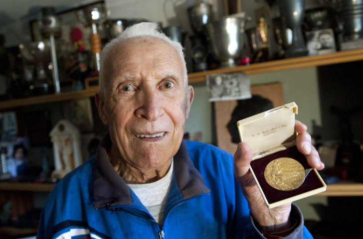 A 90-year-old Alain Mimoun with the Olympic marathon gold medal he won at Melbourne 1956 ©Getty Images