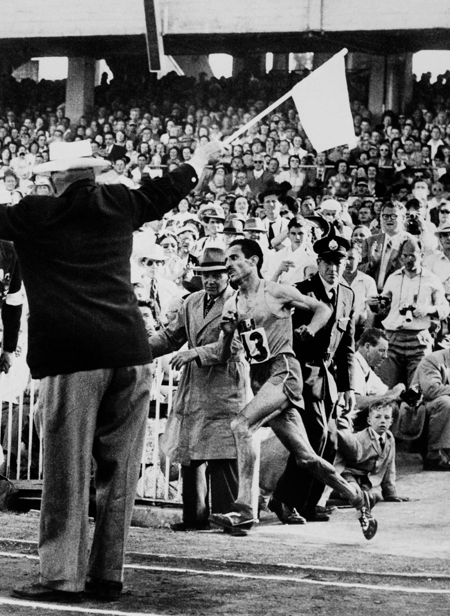 With Olympic glory awaiting, Alain Mimoun enters the Melbourne Cricket Ground in 1956 as 110,000 spectators make a noise he later compared to an