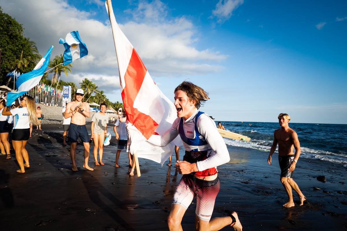 England's Sam Norton collects his flag on his way to third place in the men's paddleboard prone distance race ©ISA