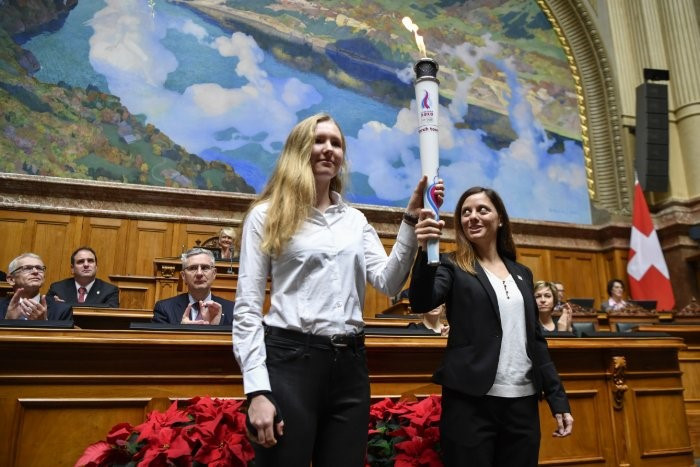 Virginie Faivre and Caroline Ulrich carry the Youth Olympic flame at the National Council ©Lausanne 2020