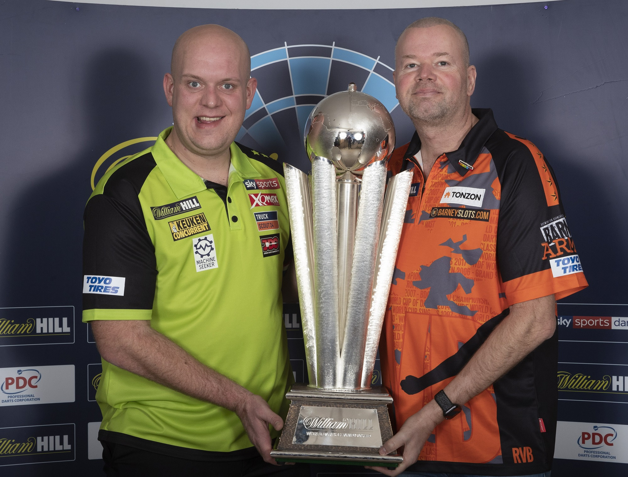 Current PDC World Champion Michael Van Gerwen, left, pictured with the trophy that he will defend at the Championships that start on Friday alongside fellow Dutchman and past winner Raymond Van Barneveld, whose last Championship this will be ©PDC