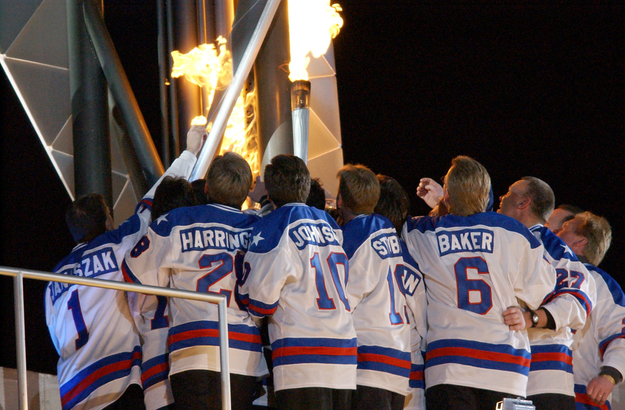The 1980 US hockey team hold the Olympic Torch during the Opening Ceremony of the 2002 Winter Olympics in Salt Lake City ©John MacDougall/AFP via Getty Images