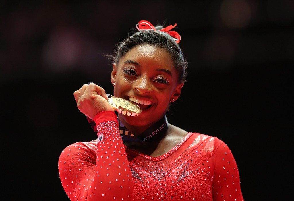 American Simone Biles made history by claiming a third straight women's all-around title at Glasgow 2015