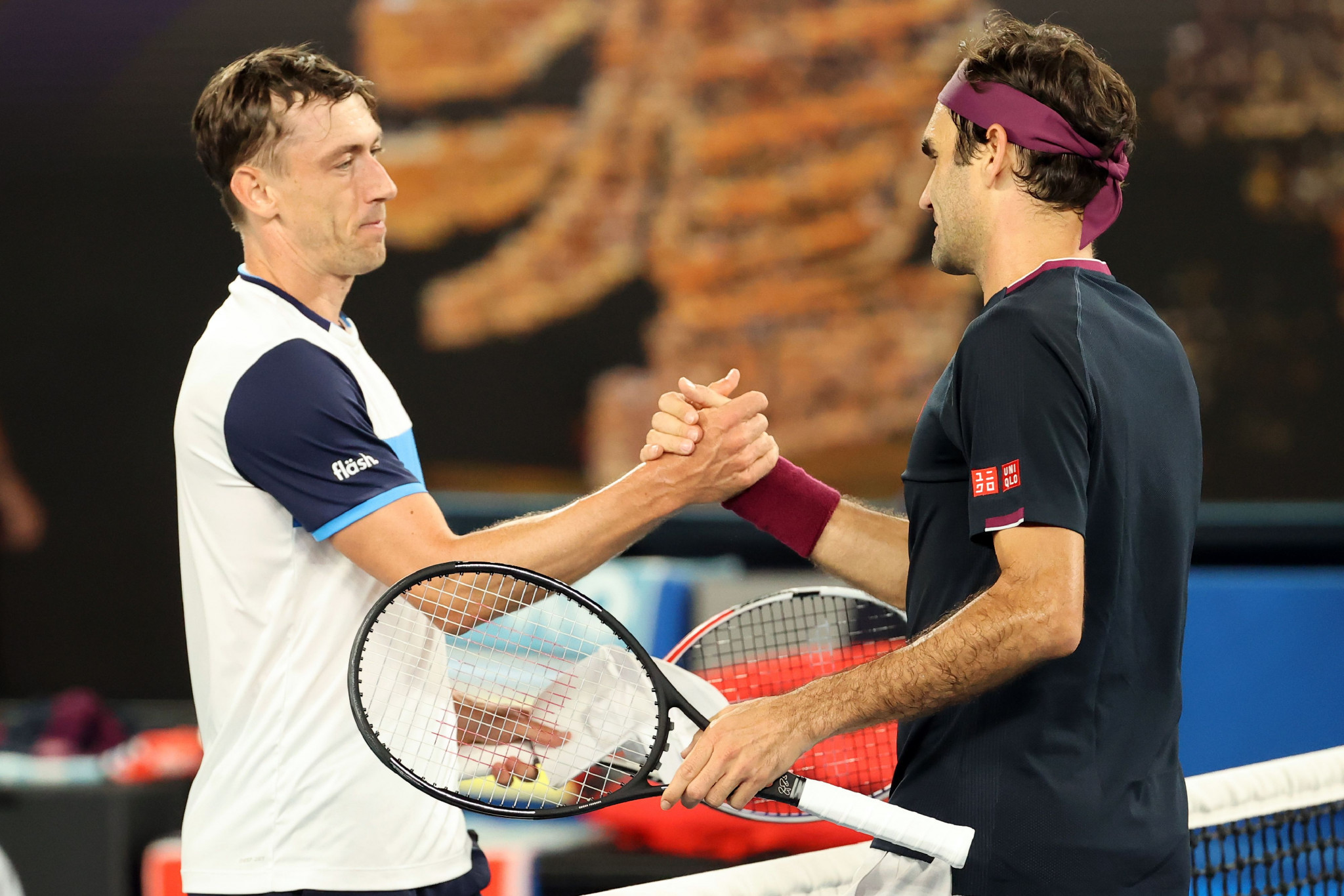 Australia's John Millman, left, shakes hands with Roger Federer after losing his Australian Open third round match on a tie-breaker in Melbourne - after which allegations were made that he had been attempting to tamper with the balls before he served them ©Getty Images